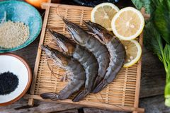 Fresh raw prawns set. Fresh raw prawns set with vegatables on the bamboo basket ready for cooking Stock Photography
