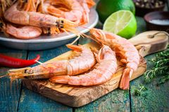 Fresh raw prawns on a wooden cutting board with salt, pepper, lime. On a rustic table Stock Photos