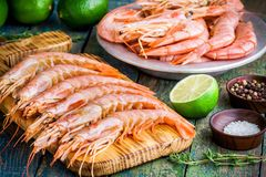 Fresh raw prawns on a wooden cutting board with salt, pepper, lime Stock Image