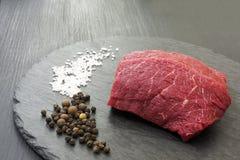 Fresh raw Prime Black Angus beef steaks on black stone board.  Stock Photography
