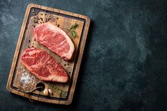 Fresh raw Prime Black Angus beef steaks with spices on wooden board: Striploin, Rib Eye. Top view with copy space. On a dark backg royalty free stock photo