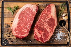 Fresh raw Prime Black Angus beef steaks with spices on wooden board: Striploin, Rib Eye. Top view. On a dark background.  royalty free stock photo