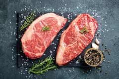 Fresh raw Prime Black Angus beef steaks on stone board: Striploin, Rib Eye. Top view. On a dark background royalty free stock photo