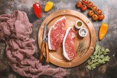 Fresh raw beef steaks. Fresh raw Prime Black Angus beef strip steaks on metal plate over dark rustic concrete background, top view. Ingredients set for making Royalty Free Stock Image