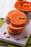 Fresh raw pumpkin. On board on wooden background. Selective focus Stock Photo