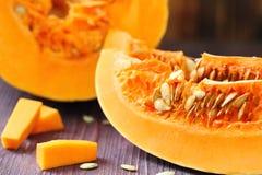 Fresh raw pumpkin. Closeup on wooden background Stock Image