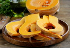 Fresh raw pumpkin. Sliced on a wooden table Stock Images