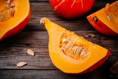 Raw pumpkin slices with seeds on a wooden background. Fresh raw pumpkin slices with seeds on a wooden background Royalty Free Stock Photos