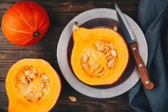 Raw pumpkin slices with seeds on a wooden background. Fresh raw pumpkin slices with seeds on a wooden background Stock Photography
