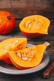 Raw pumpkin slices with seeds on a wooden background. Fresh raw pumpkin slices with seeds on a wooden background Stock Image