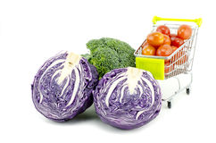 Fresh raw purple cabbage, cherry tomatoes on trolley and broccoli. Isolated white background Stock Photos