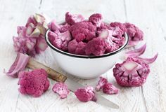 Fresh raw purple cauliflower. On a wooden board close up Royalty Free Stock Photography