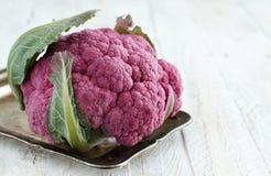 Fresh raw purple cauliflower. On a wooden board close up Stock Photo