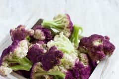 Fresh raw purple cauliflower. On a wooden board close up Stock Photography