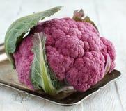 Fresh raw purple cauliflower. On a wooden board close up Royalty Free Stock Photo