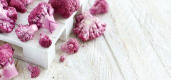 Fresh raw purple cauliflower. On a wooden board close up Stock Image