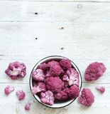 Fresh raw purple cauliflower. On a wooden board top view Royalty Free Stock Photography