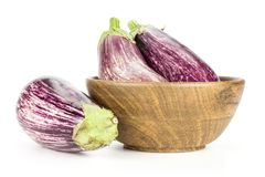 Fresh Raw purple striped Eggplant isolated on white. Three striped purple eggplants in a wooden bowl isolated on white background Royalty Free Stock Image