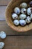 Fresh raw quail eggs in a basket. Top view Stock Photos
