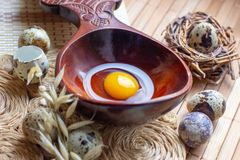Fresh raw quail eggs in wooden spoon on rustic straw and wooden vintage background stock images