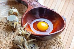 Fresh raw quail eggs in wooden spoon on rustic straw and wooden vintage background. stock images