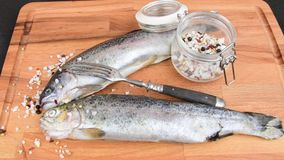 Fresh raw rainbow trouts with spices and fork on wooden board. Healthy food and dieting concept. Close-up.  stock video