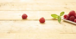 Fresh and raw raspberries and raspberries on wooden background. Berries lieing on nice old table with leaf of mint Royalty Free Stock Photos