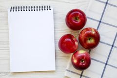 Fresh raw red apples and blank notepad on white wooden background, overhead view. Flat lay, from above, top view. Space for text royalty free stock photography