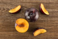 Fresh raw red blue plum on brown wood. Red blue plums set table top isolated on brown wood background one whole one section half three slices Stock Images