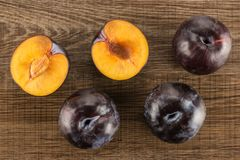 Fresh raw red blue plum on brown wood. Red blue plums three whole two sliced halves table top isolated on brown wood background Stock Image