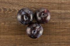 Fresh raw red blue plum on brown wood. Three red blue plums table top isolated on brown wood background round whole fresh juicy fruit Stock Image