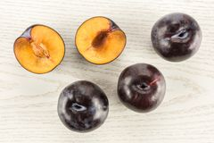 Fresh raw red blue plum on grey wood. Red blue plums three whole two sliced halves table top isolated on grey wood background Royalty Free Stock Photography