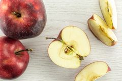 Fresh raw red delicious apple on grey wood. Sliced red delicious apples flatlay on grey wood background two whole one half and three slices Royalty Free Stock Image