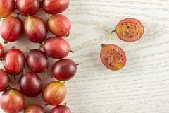 Fresh raw red gooseberry on grey wood. Lot of whole fresh red gooseberry hinnomaki variety one cut in two section halves flatlay on grey wood Royalty Free Stock Photo
