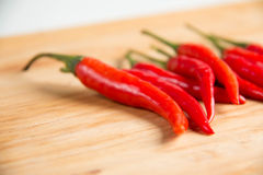 Fresh raw red hot chili peppers on wood. Closeup of  fresh raw red hot chili peppers on wood Stock Photo