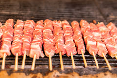 Fresh raw red meat pork breast fillets on a skewer barbecue grill grid roasts. Skewers of pork on a wooden stick. Greece, souvlaki Stock Photography