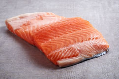 Fresh raw red salmon fillet. Fresh raw salmon fillet on grey table Royalty Free Stock Photos