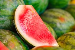 Fresh raw red watermelon on market stall and a slice of it wrapped with plastic. For display purpose Royalty Free Stock Photo
