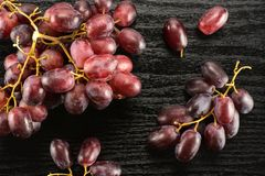 Fresh raw red wine grapes on black wood. Red globe grape berries table top isolated on black wood background fresh dark pink Royalty Free Stock Images