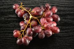 Fresh raw red wine grapes on black wood. Red globe grape rich cluster table top isolated on black wood background dark pink berries Stock Photo