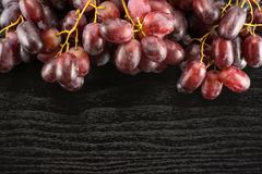 Fresh raw red wine grapes on black wood. Red globe grapes table top isolated on black wood background shiny deep pink berries stock photography
