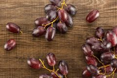 Fresh raw red wine grapes on brown wood. Red globe grape table top isolated on brown wood background deep pink berries Royalty Free Stock Photography