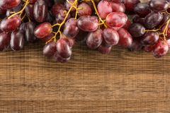 Fresh raw red wine grapes on brown wood. Red globe grapes table top isolated on brown wood background shiny deep pink berries stock image