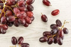 Fresh raw red wine grapes on grey wood. Red globe grape berries table top isolated on grey wood background fresh dark pink Royalty Free Stock Images