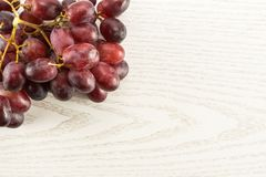 Fresh raw red wine grapes on grey wood. Red globe grape cluster table top isolated on grey wood background dark pink berries Royalty Free Stock Photography