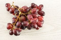 Fresh raw red wine grapes on grey wood. Red globe grape rich cluster table top isolated on grey wood background dark pink berries Stock Photography