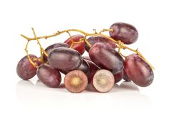 Fresh raw red wine grapes isolated on white. Red globe grape cluster and one berry cut in half isolated on white background fresh shiny dark pink two section Royalty Free Stock Photography