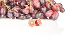 Fresh raw red wine grapes isolated on white. Red globe grape cluster and one fresh shiny dark pink berry cut in half isolated on white background Stock Photography