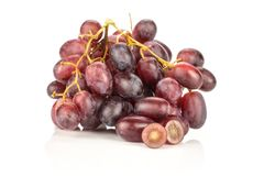 Fresh raw red wine grapes isolated on white. Red globe grape cluster with one sliced berry isolated on white background fresh shiny dark pink Royalty Free Stock Image
