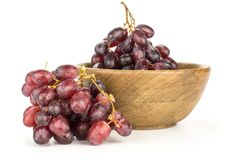 Fresh raw red wine grapes isolated on white. Red globe grape cluster in a wooden bowl isolated on white background shiny dark pink berries Royalty Free Stock Photography